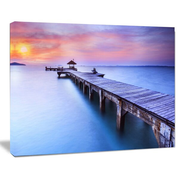 Beach with Blue Waters and Wood Bridge Sea Pier Photographic Print on Wrapped Canvas by Design Art