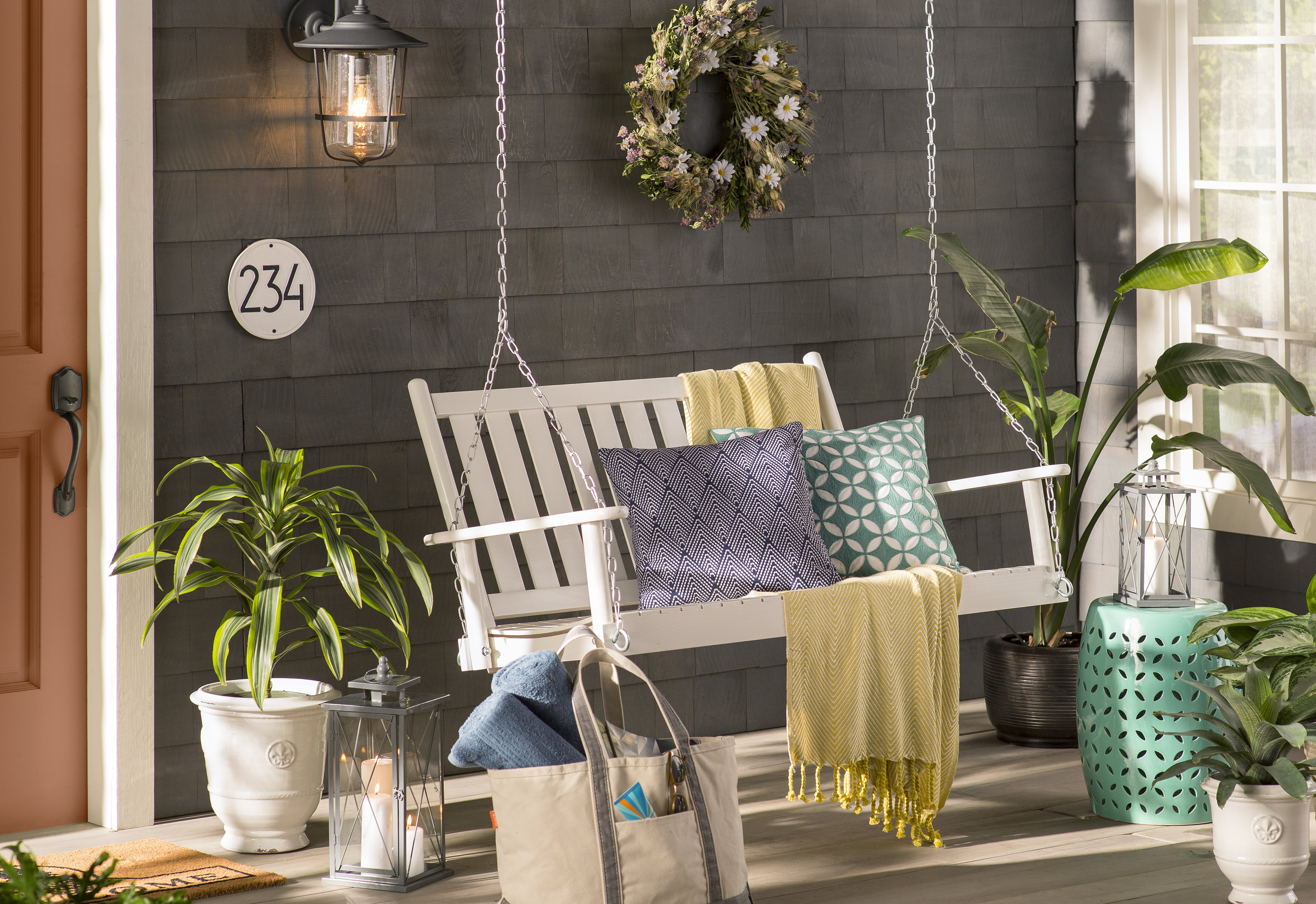 classic white porch swing with throw pillows and blankets