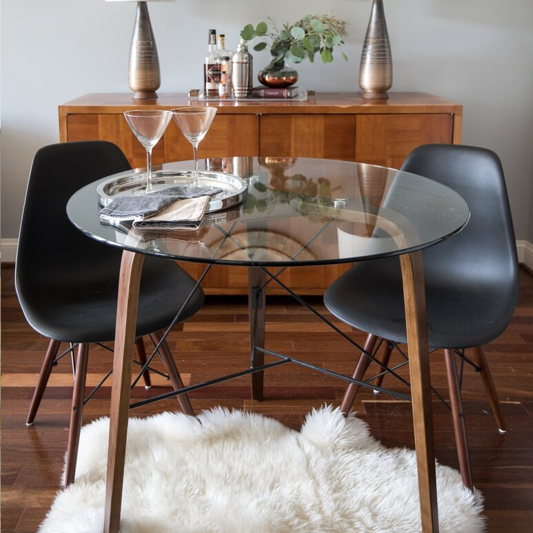 Black Eiffel Chairs With Wood Legs Around A Small Round Glass Topped Table