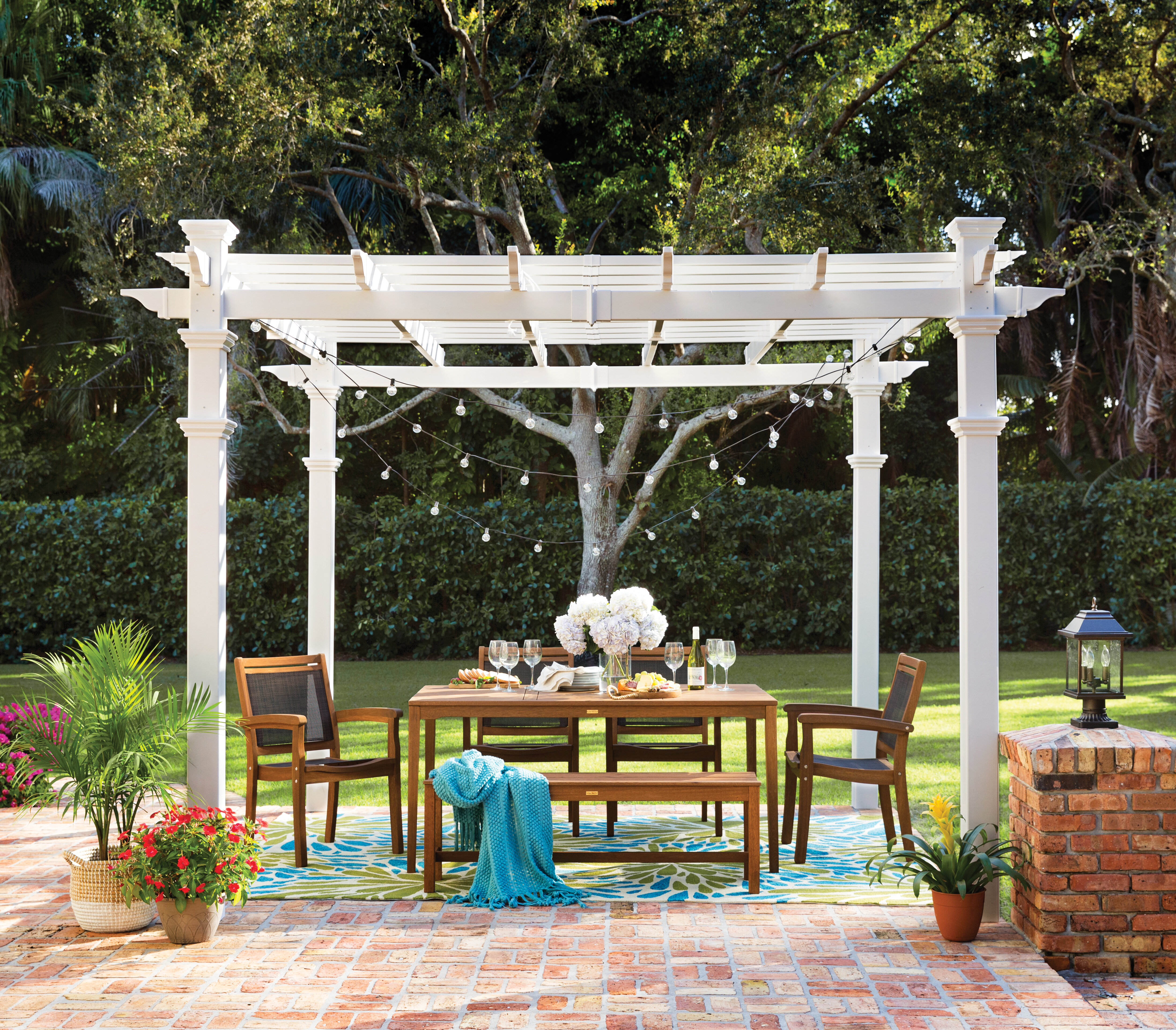brick patio dinner set shaded by a white pergola decorated with string lights