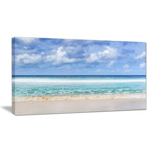 Tranquil Beach Under White Clouds Photographic Print on Wrapped Canvas by Design Art