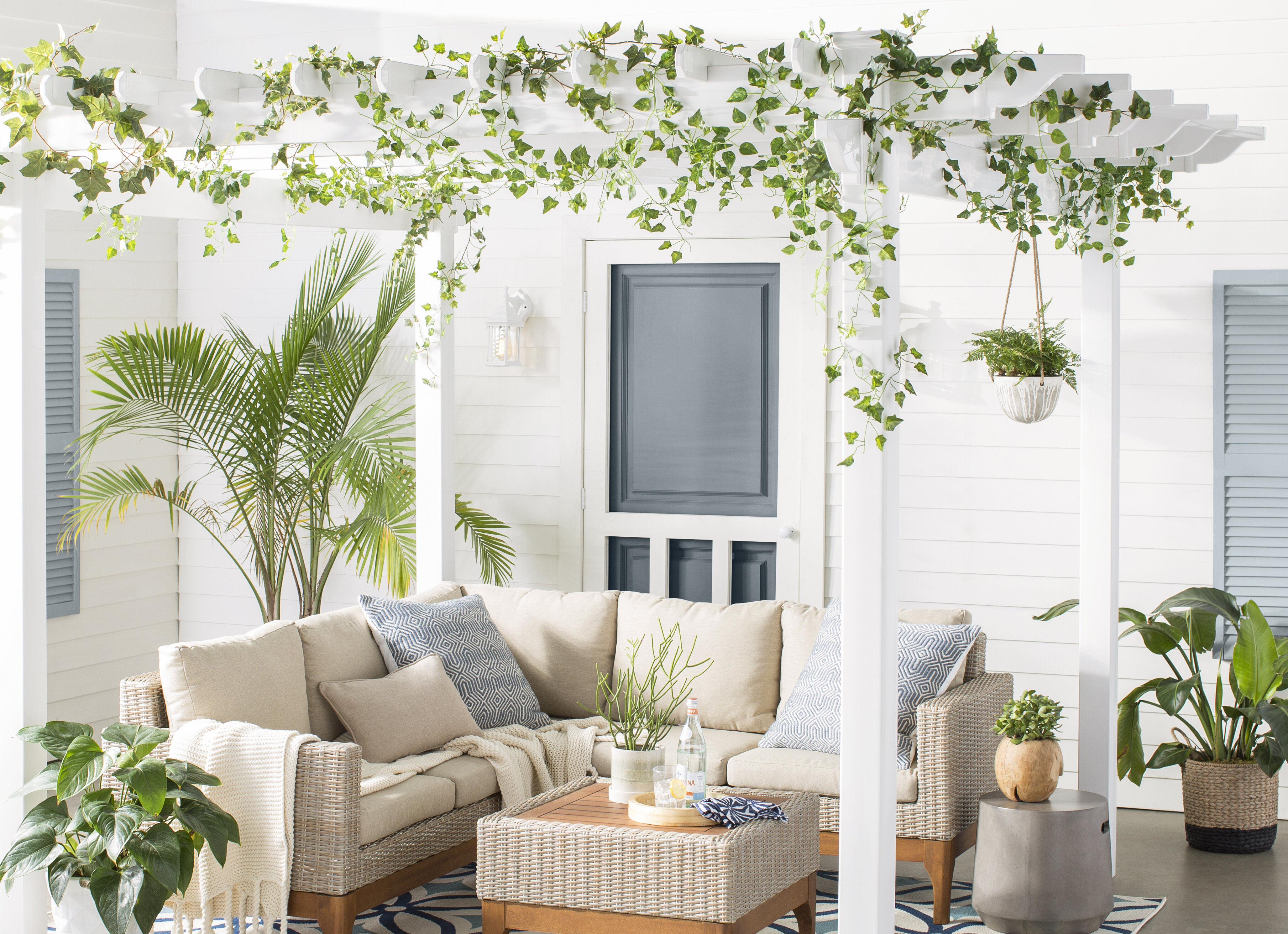 Clean white patio shaded by a pergola decorated with vines